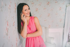 红色礼服电话谈话的少妇 智能手机电话 女孩S邮件和谈话与机动性 免版税图库摄影