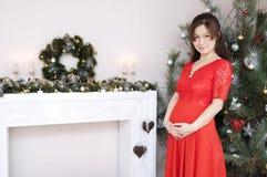 红色礼服画象的怀孕的美丽的女孩在圣诞节内部举行的心脏 免版税图库摄影