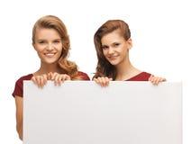 红色礼服的两个十几岁的女孩有空白的委员会的 免版税图库摄影