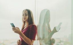 红色礼服的企业夫人有在办公室窗口附近的智能手机的 免版税库存图片