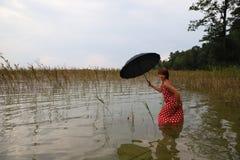 红色礼服的俏丽的半裸的性感的妇女在湖 免版税图库摄影