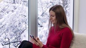 红色礼服的俏丽的女孩坐窗台使用智能手机 外部冬天 股票视频