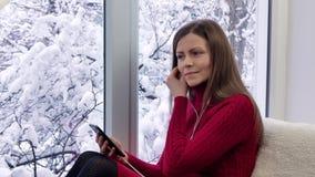 红色礼服的俏丽的女孩坐窗台使用有耳机的智能手机 外部冬天 股票录像