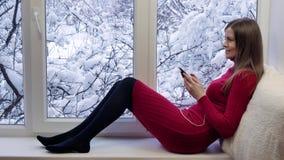 红色礼服的俏丽的女孩坐窗台使用有耳机的智能手机 外部冬天 股票视频