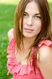 红色礼服的俏丽的妇女坐公园 免版税库存照片