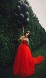 红色礼服的华美的妇女有黑气球的 图库摄影