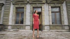 红色礼服的可爱的女孩在一个老庄园的阳台去 股票录像