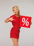 红色礼服的可爱的妇女有百分号的 免版税库存照片