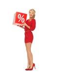 红色礼服的可爱的妇女有百分号的 免版税图库摄影