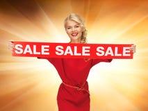 红色礼服的可爱的妇女有销售标志的 免版税库存照片