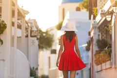红色礼服的圣托里尼旅行旅游深色的妇女参观著名白色Oia村庄的 免版税图库摄影