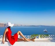 红色礼服的圣托里尼旅行旅游深色的妇女参观著名白色Oia村庄的 库存照片