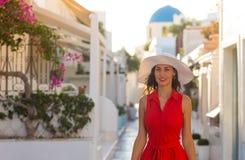 红色礼服的圣托里尼旅行旅游深色的妇女参观著名白色Oia村庄的 图库摄影
