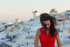 红色礼服的圣托里尼旅行旅游深色的妇女参观著名白色Oia村庄的 免版税库存照片