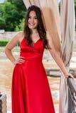 红色礼服的女孩和牙在庭院里微笑摆在并且握在臀部的一只手在铁篱芭和帷幕前面 免版税库存照片