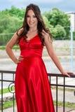 红色礼服的女孩和牙微笑摆在并且握在臀部的一只手在铁篱芭前面 图库摄影