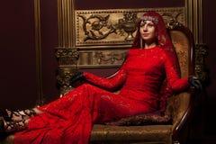 红色礼服的女孩在内部 免版税图库摄影