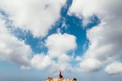 红色礼服的女孩在岩石和峭壁中沿海阿尔加威 免版税库存图片
