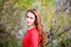 红色礼服的女孩在庭院里 图库摄影
