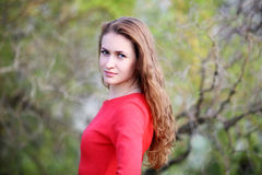 红色礼服的女孩在庭院里 库存图片