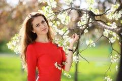 红色礼服的女孩在庭院里 免版税库存图片