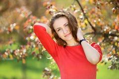 红色礼服的女孩在庭院里 免版税库存照片