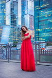 红色礼服的女孩在摩天大楼背景  sta 图库摄影