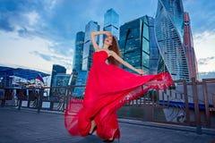 红色礼服的女孩在莫斯科城市的背景 免版税库存图片