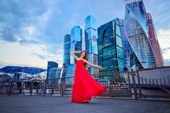 红色礼服的女孩在莫斯科城市的背景 图库摄影