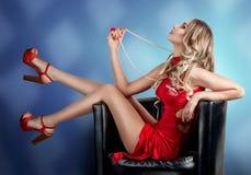 红色礼服的女孩坐与您的脚的一把椅子 免版税库存照片