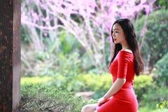 红色礼服的女孩坐长沙发 免版税库存图片