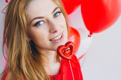 红色礼服的女孩有以心脏的形式气球的 库存照片