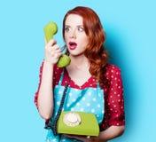 红色礼服的女孩有绿色拨号电话的 库存图片