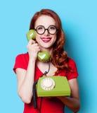 红色礼服的女孩有绿色拨号电话的 免版税库存照片