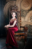 红色礼服的女王/王后坐王位 球次幂终止符号字 库存照片