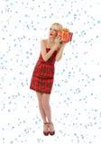 红色礼服的妇女与礼品。 雪花 免版税图库摄影