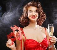 红色礼服的妇女在与面具的狂欢节 免版税库存图片