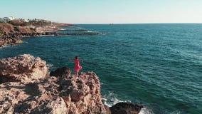 红色礼服的妇女在山峭壁上面用手单独在空气 拍动她的礼服的风,当她享受太阳和温暖的windF时 影视素材
