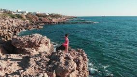红色礼服的妇女在山峭壁上面用手单独在空气 拍动她的礼服的风,当她享用太阳和温暖的风时 股票录像