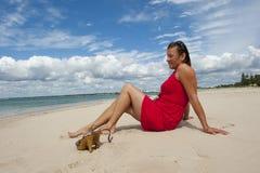 红色礼服的妇女在海滩 免版税图库摄影