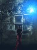 红色礼服的妇女在被困扰的房子 库存照片