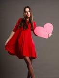 红色礼服的妇女拿着心脏标志 库存照片