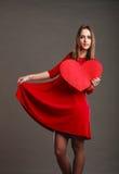 红色礼服的妇女拿着心脏标志 免版税库存照片