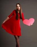 红色礼服的妇女拿着心脏标志 图库摄影