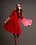 红色礼服的妇女拿着心脏标志 免版税库存图片