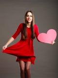 红色礼服的妇女拿着心脏标志 库存图片