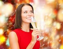红色礼服的妇女有一杯的香槟 免版税库存图片