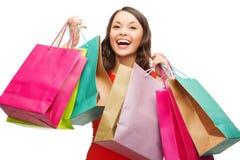 红色礼服的妇女有五颜六色的购物袋的 图库摄影