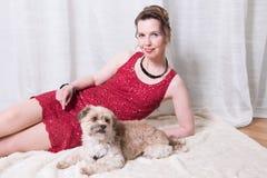 红色礼服的妇女有在毯子的狗的 免版税图库摄影