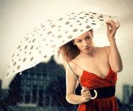 红色礼服的妇女有在雨下的伞的在夜城市背景 免版税库存图片
